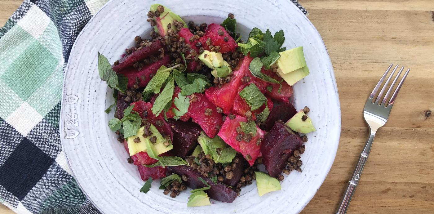 a vivid beet salad in a white bowl on a wooden table