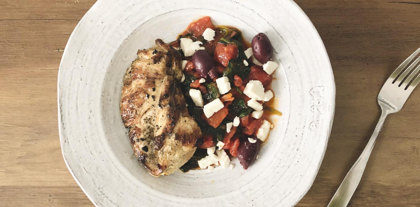 grilled chicken breast atop mixture of olives, feta, tomatoes, spinach