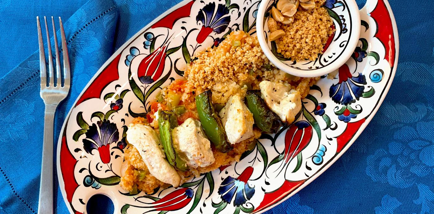 skewer threaded with alternating pieces of grilled chicken and green bell peppers, atop a bed of bulgur on a colorful platter