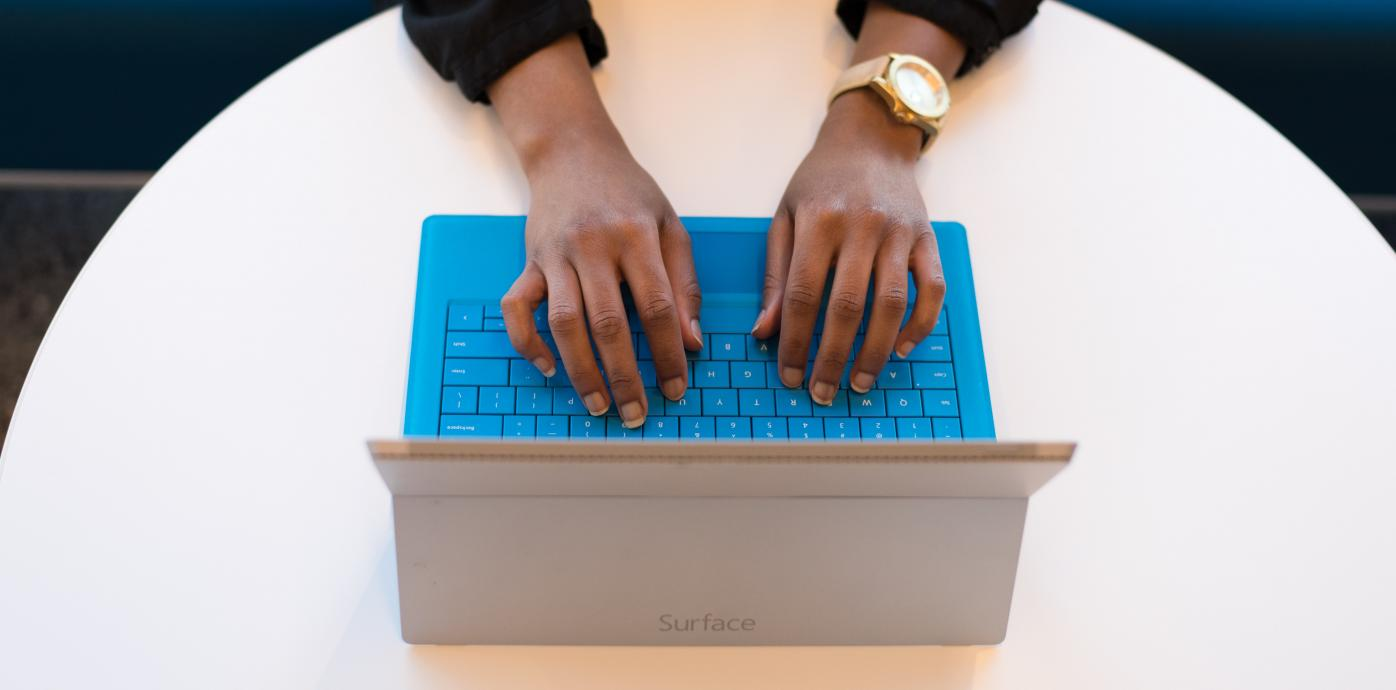 hands typing over the keys of a laptop