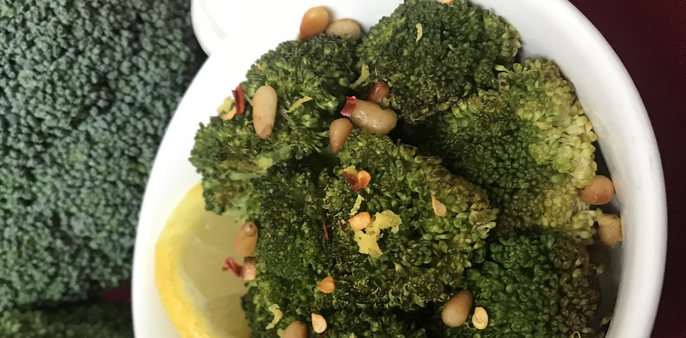 Broccoli in a dish with lemon and pine nuts