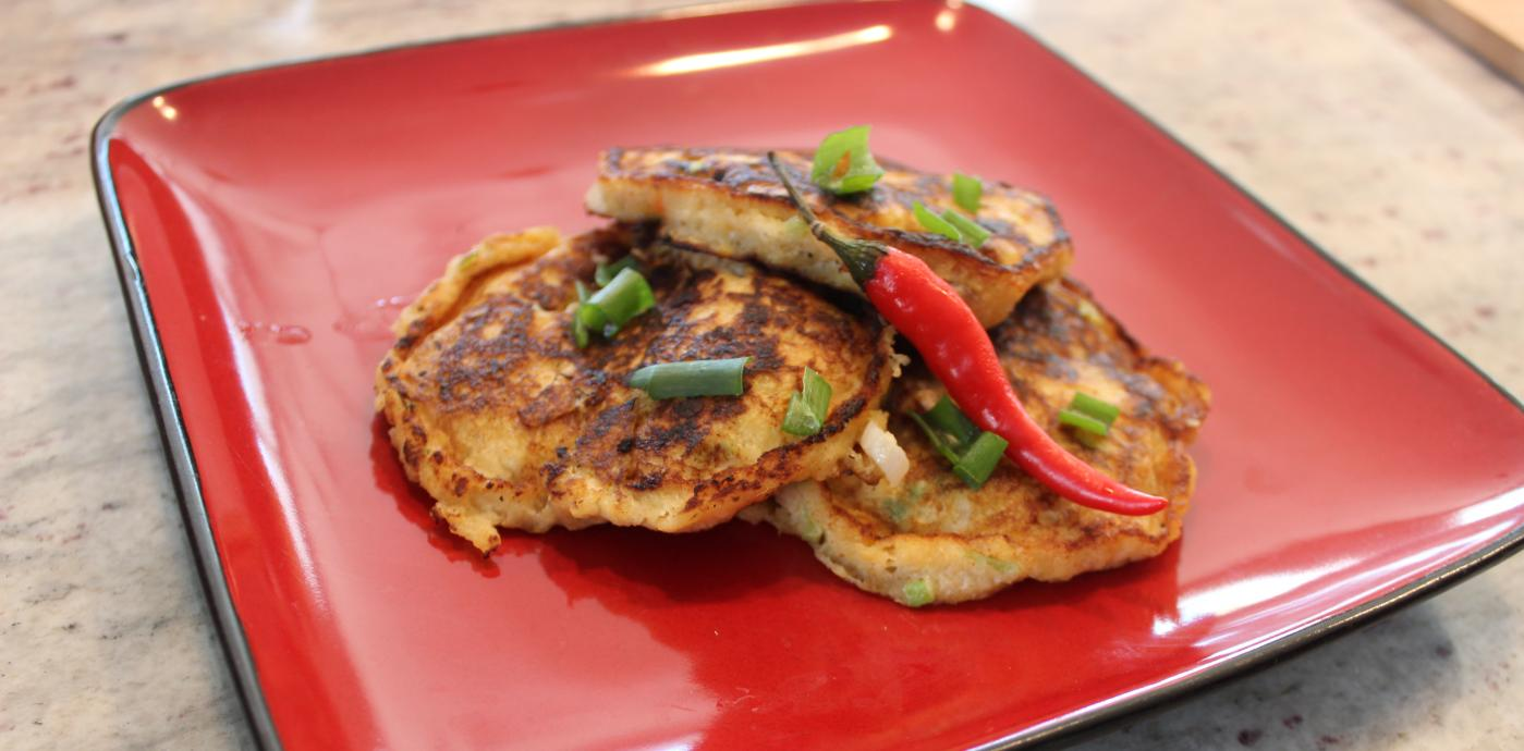 plantain pancakes on a red plate garnished with a chile pepper