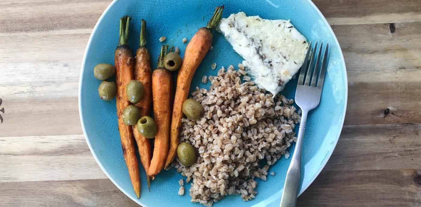 Whole roasted carrots topped with olives, next to a serving of farro grains and a fillet of fish