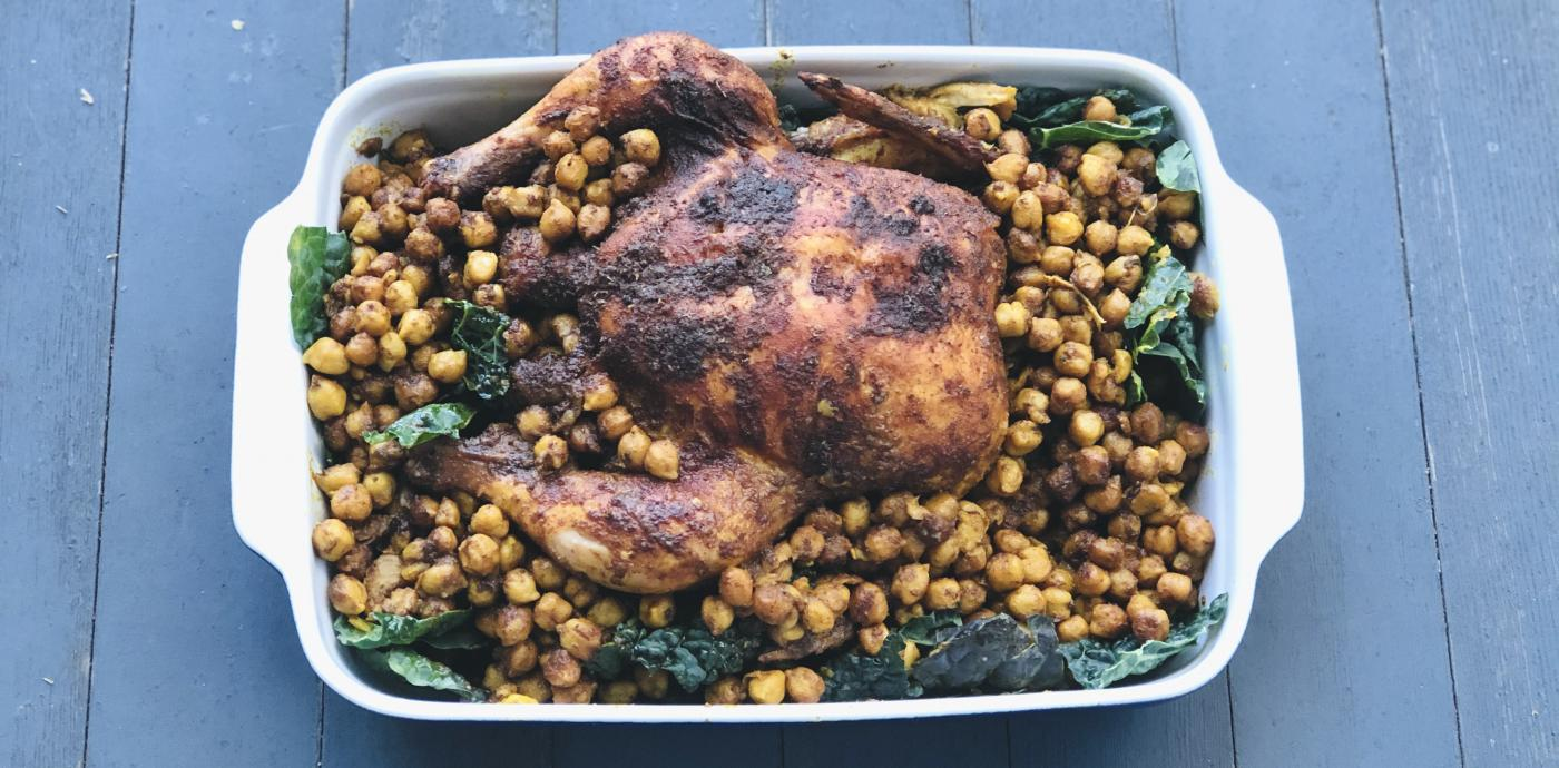 roasted whole chicken over a bed of chickpeas and kale