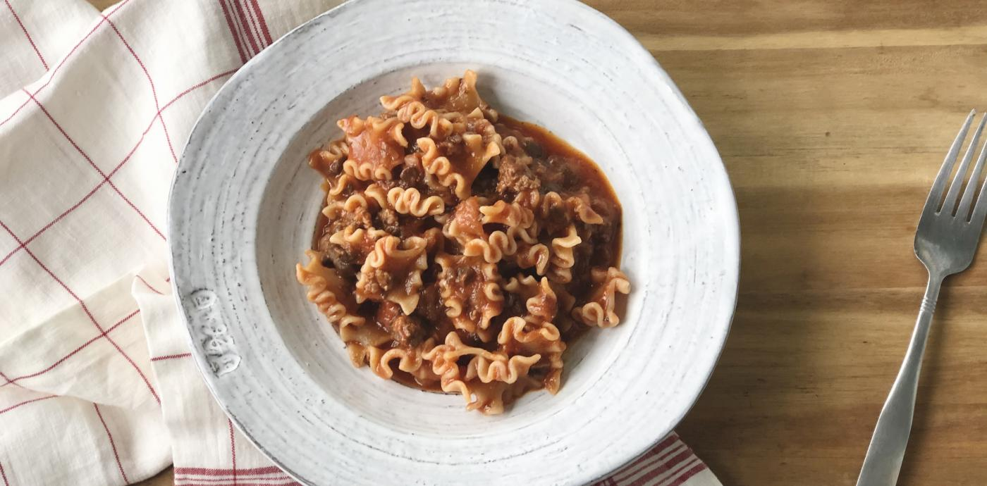 bowl of pasta with tomato meat sauce on a wooden table