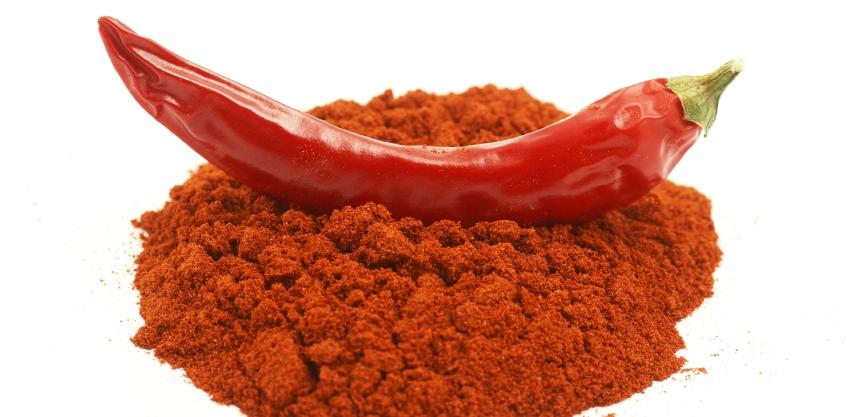 a pile of chili powder with a chili pepper sitting on top