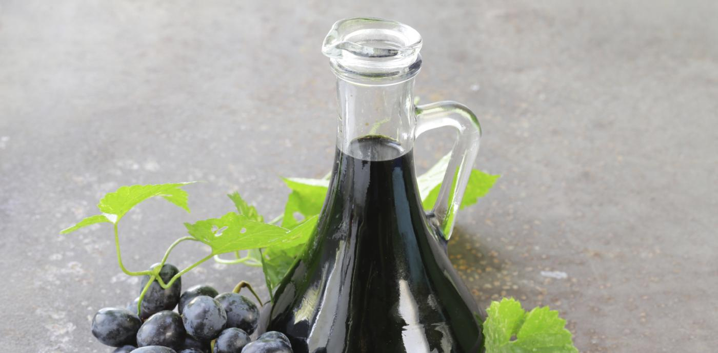 jar of balsamic vinegar next to grapes