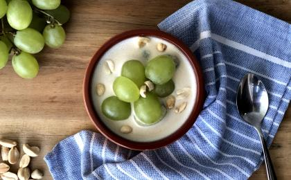 creamy soup topped with green grapes on a wooden surface