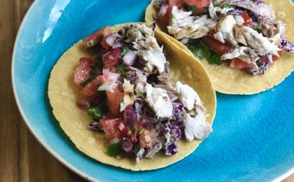 2 fish tacos topped with salsa on a blue plate