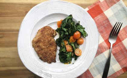 breaded chicken next to cooked greens and tomatoes on a white plate