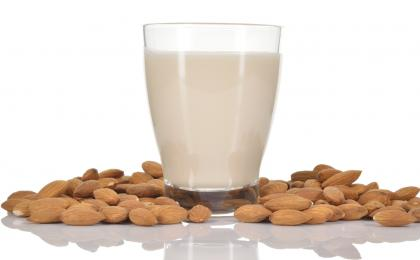 Glass of almond surrounded by almonds