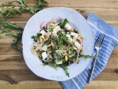 leafy quinoa salad in a white bowl