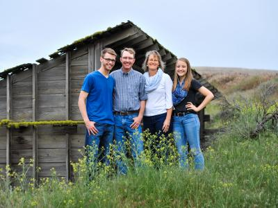 Farming family standing in front of barn
