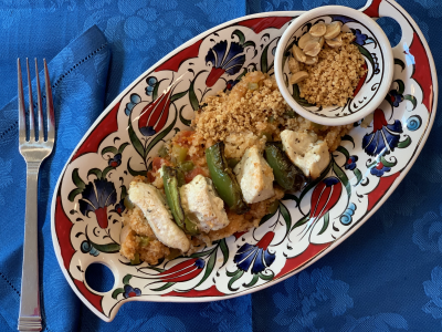 grain salad and grilled chicken kebab atop a colorful stoneware dish