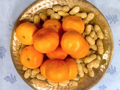 a large gold serving bowl filled with peanuts and clementines