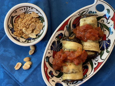 two small eggplant rolls topped with tomato sauce served in a colorful dish