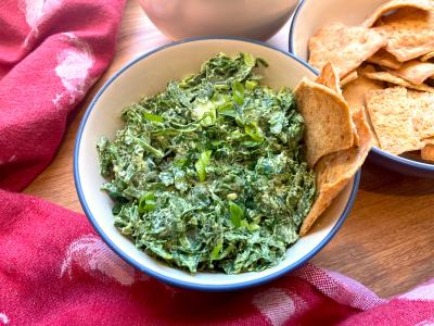 Greek spinach salad in a dish on a table with pita
