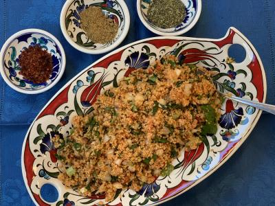 Kisir (bulgur salad) in serving dish with spices on the table