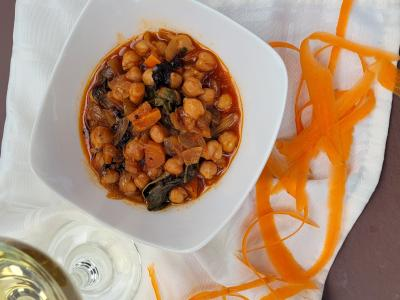 Chickpeas in a dish with a glass of wine