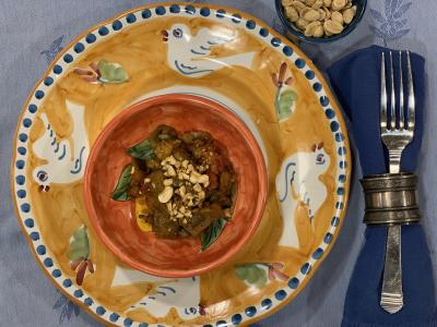 Warm caponata with toasted peanuts on plate with side of peanuts