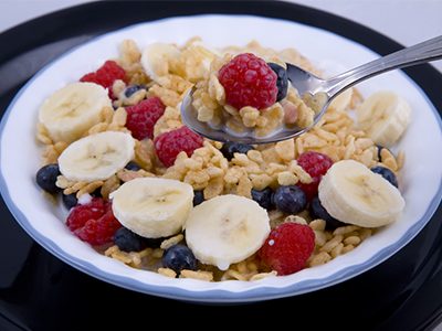 Bowl of oatmeal topped with berries and sliced banana
