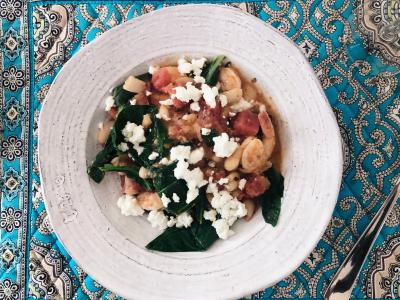 shrimp, greens, tomatoes, and feta in a bowl