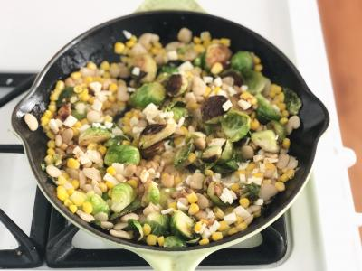 skillet filled with corn, butter beans, and brussels sprouts