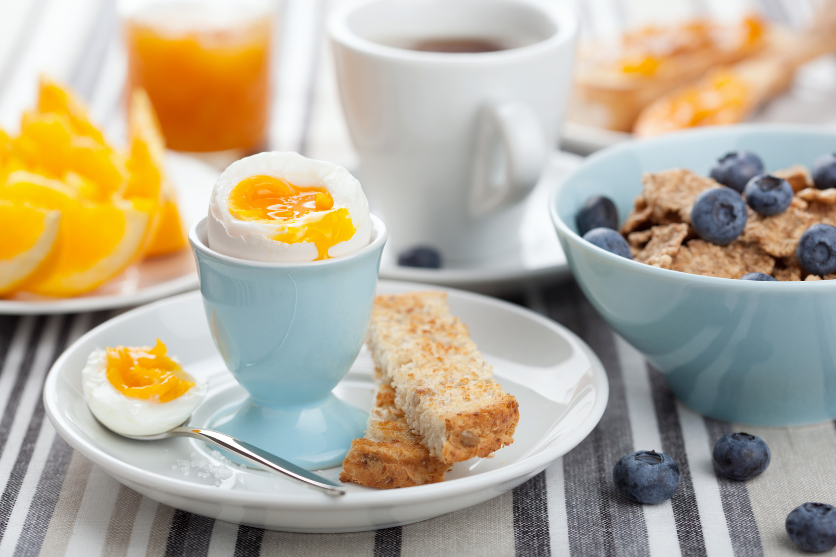 soft boiled egg in an egg cup with toast, coffee, and oranges