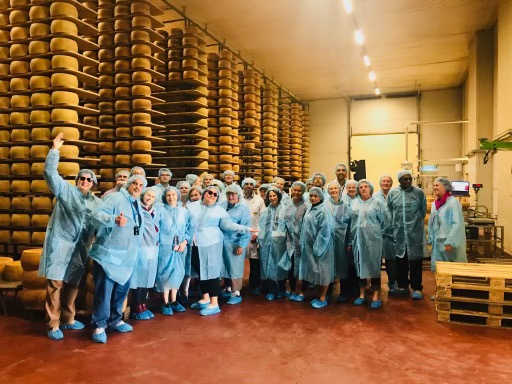 standing in front of a wall of cheese wheels