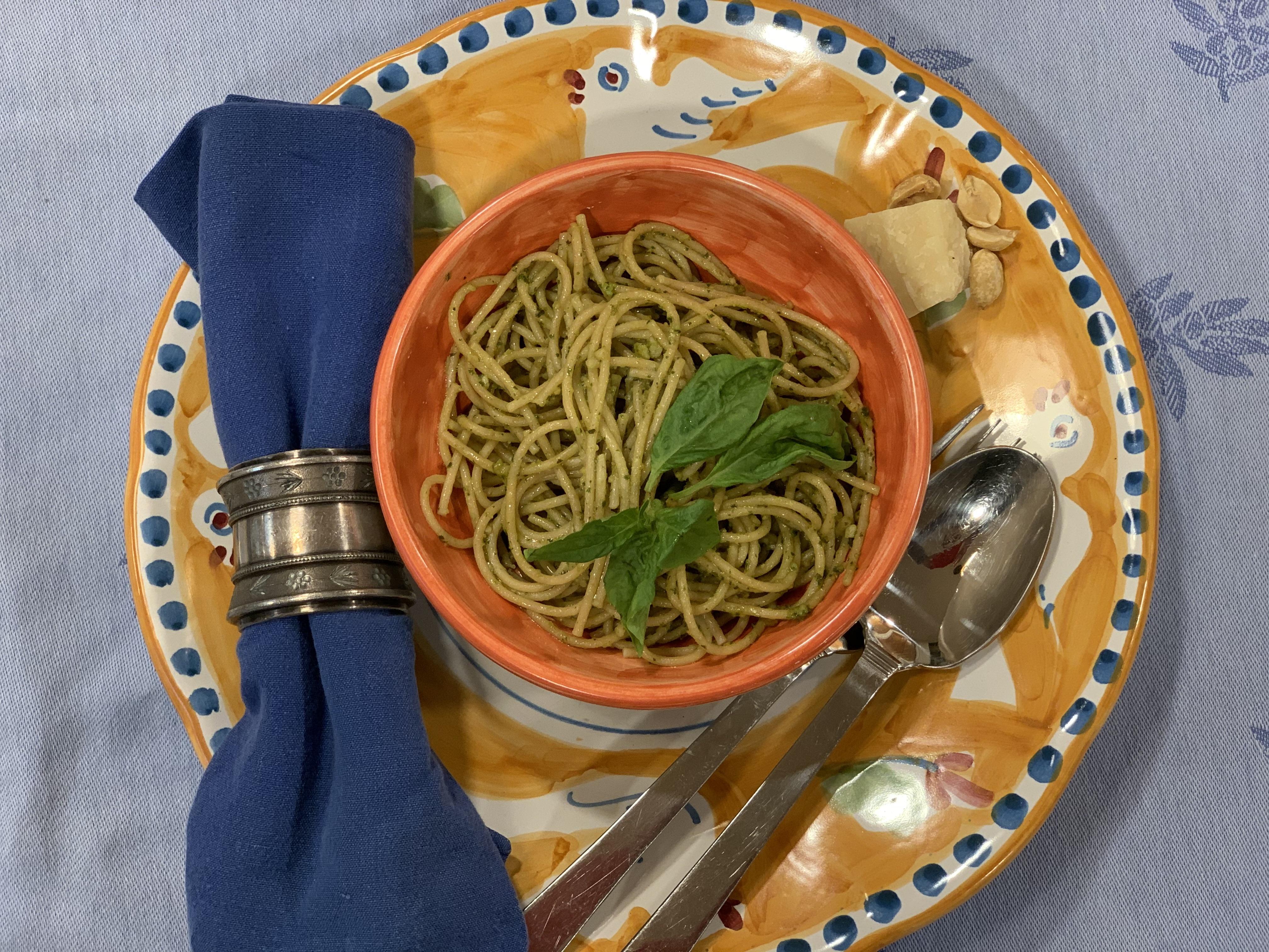 bowl of spaghetti with pesto sauce atop a colorful dish
