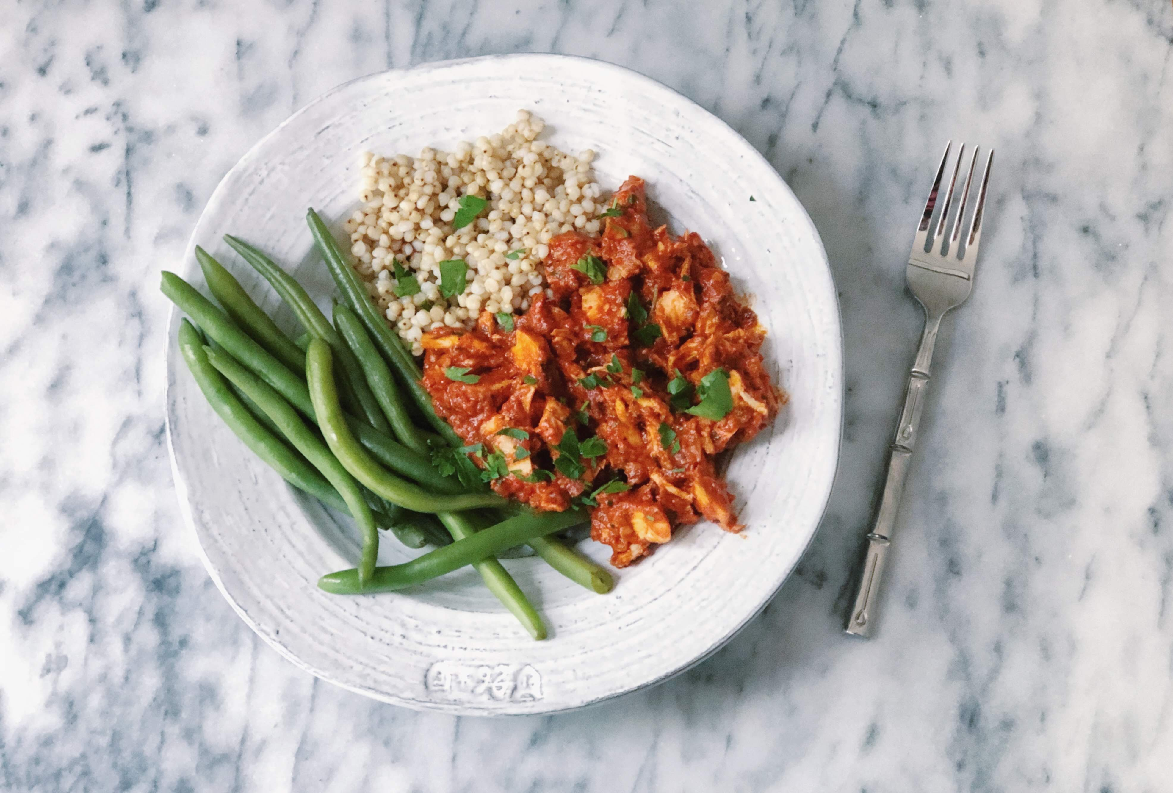 chicken in romesco sauce served atop sorghum and green beans