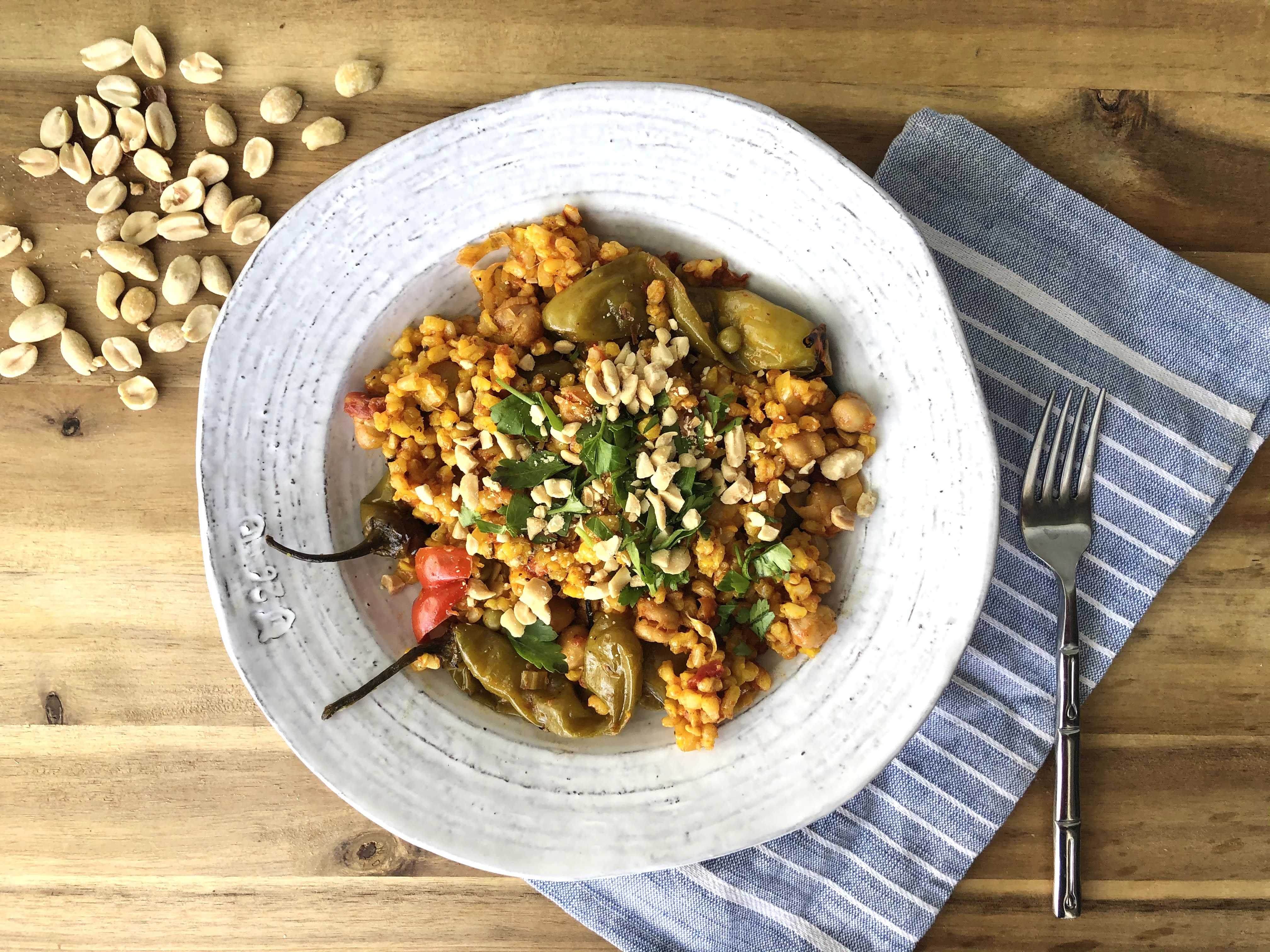 vegetable paella in a rustic white bowl atop a wooden surface with peanuts scattered in the background