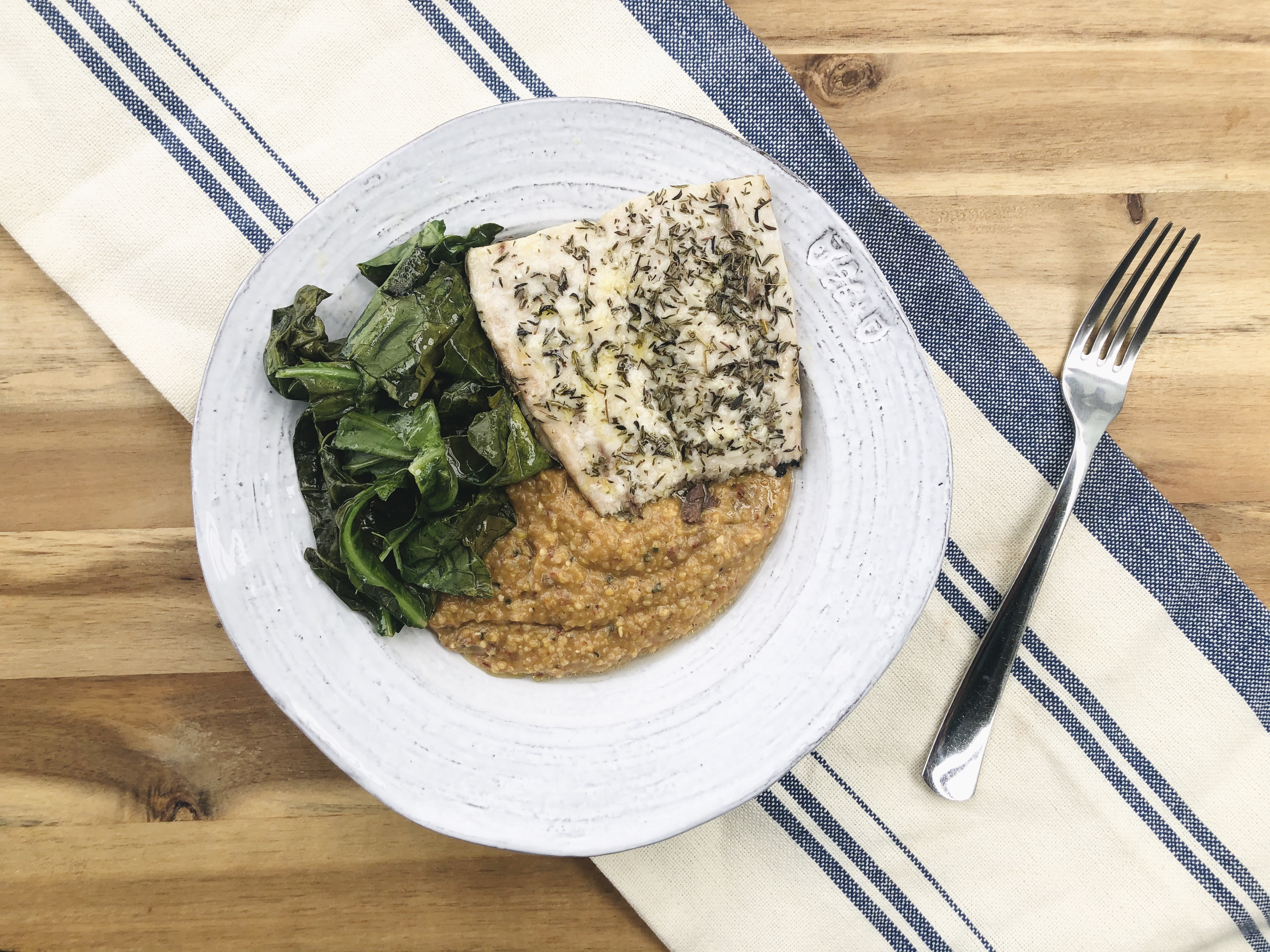 bowl of polenta on a table topped with fish and greens