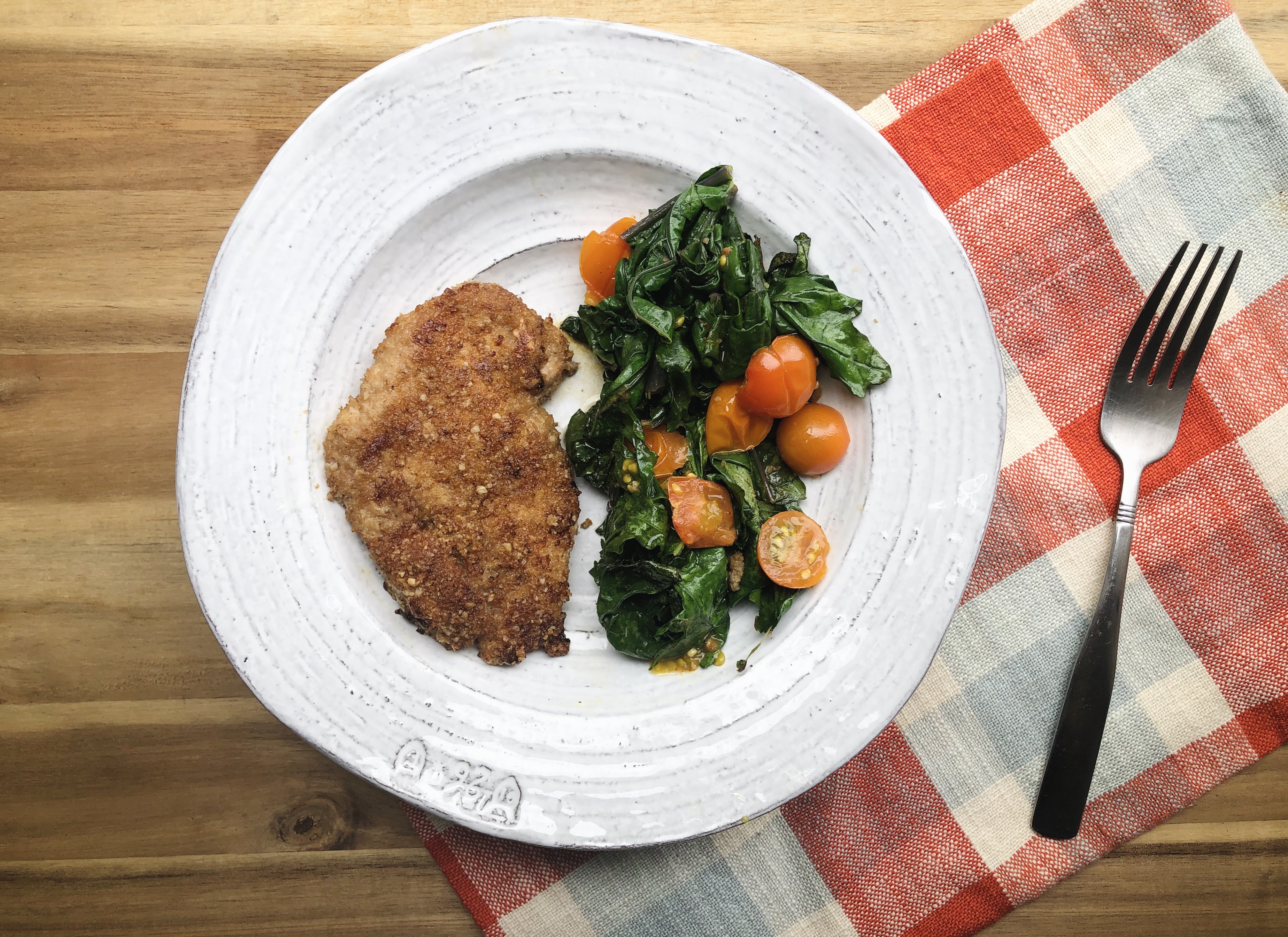 walnut crusted chicken with collards on white plate