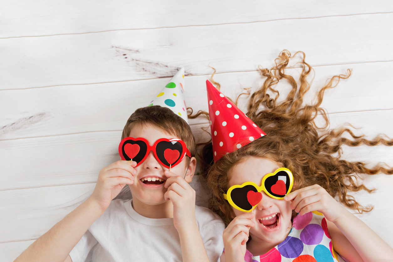 boy and girl laughing with heart sunglasses and party hats